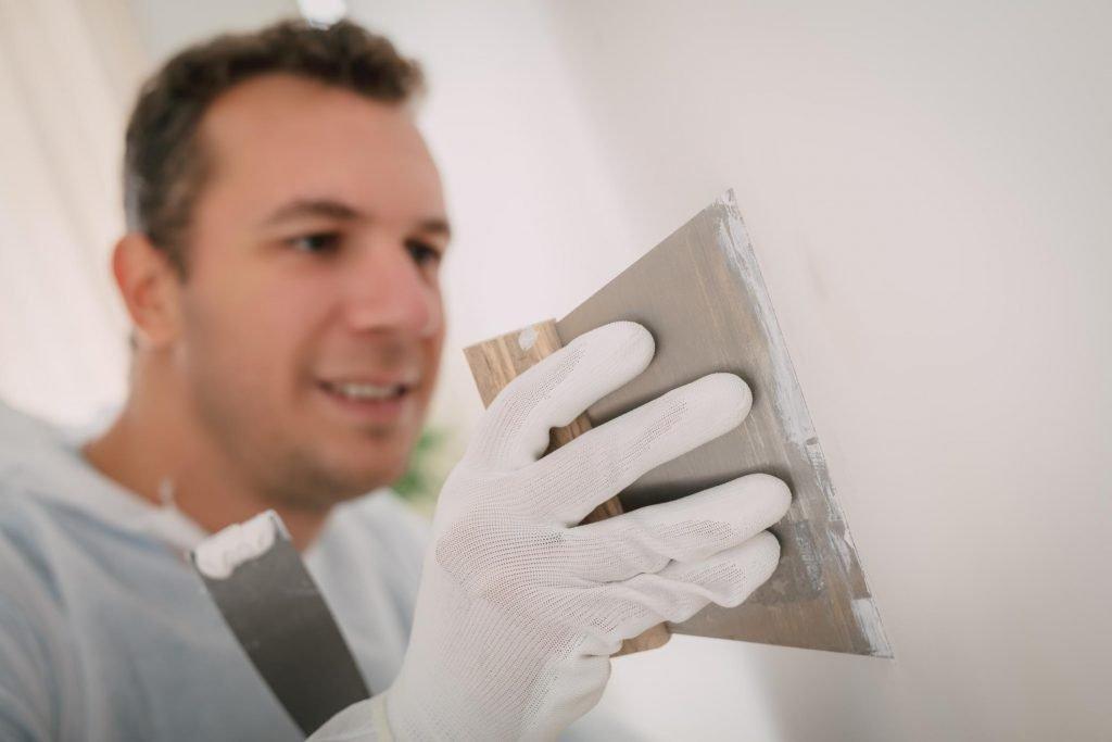 man applying patty on the wall