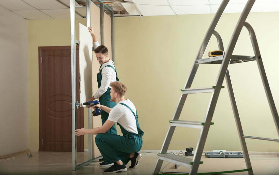 men installimng a drywall indoors