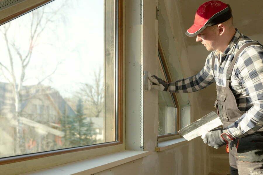 man applying patty on the wall near the window