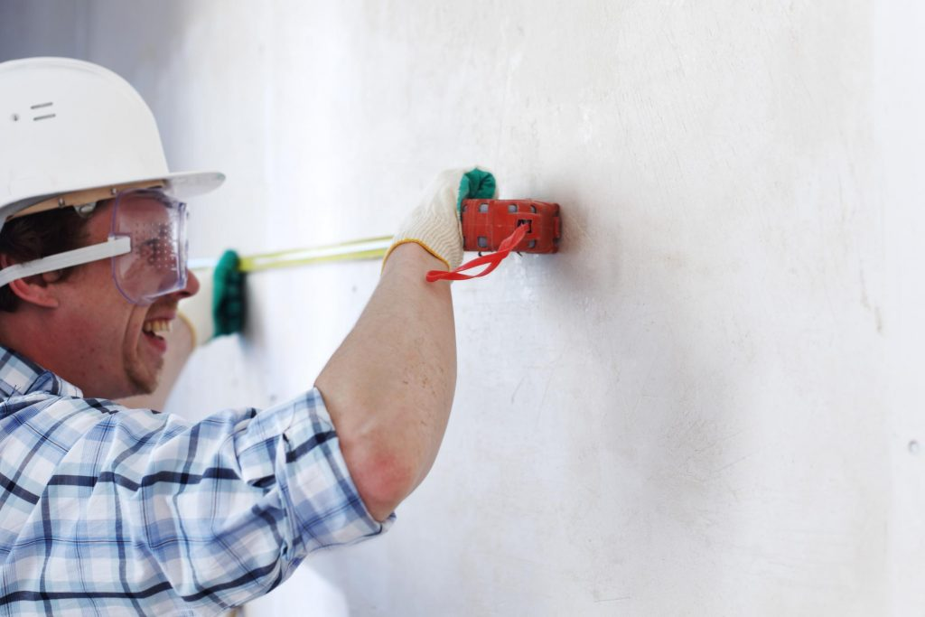 man smiling while measuring the wall