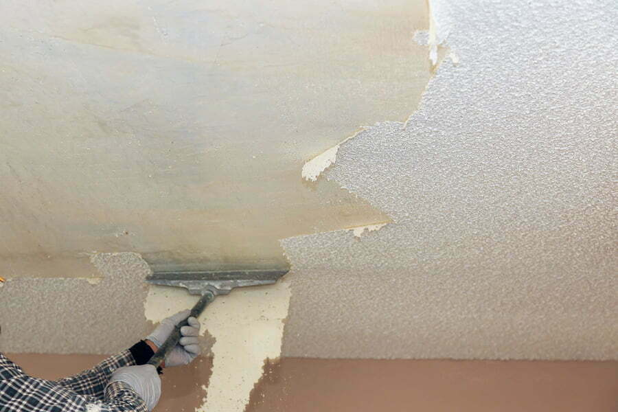 man scraping off the popcorn ceiling