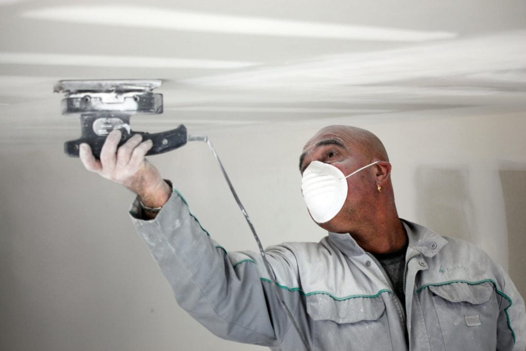 man applying patty on the ceiling